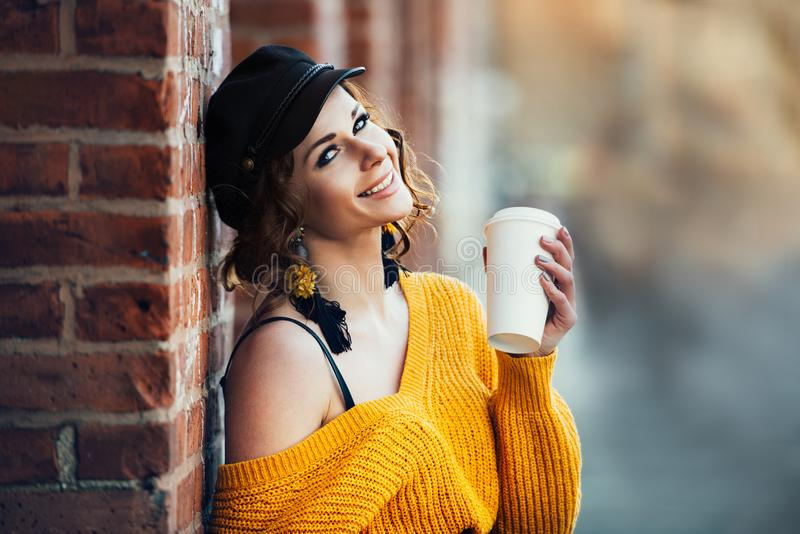 Bella tazza di caffè di plastica sorridente felice della carta della tenuta della donna all'aperto sul parco della via della citt immagine stock