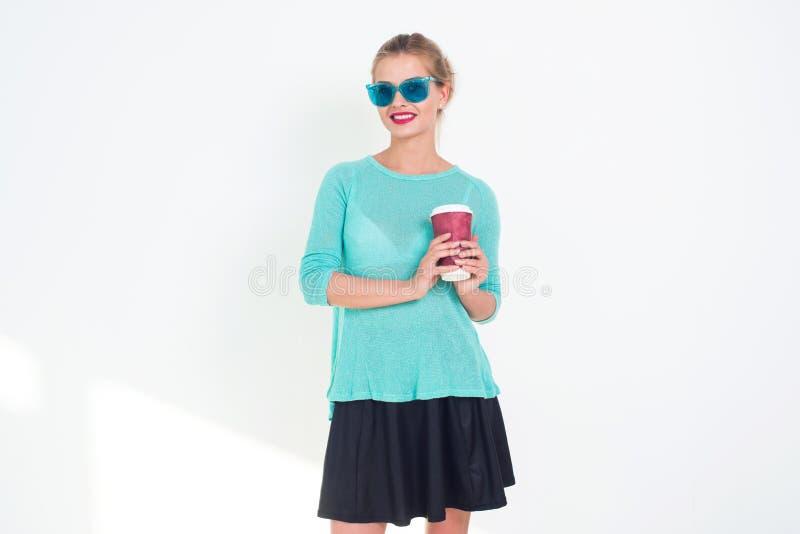 Bella tazza di tenuta femminile di caffè caldo occhiali da sole blu alla moda durare, da andare, blusa e trucco luminoso con immagine stock libera da diritti