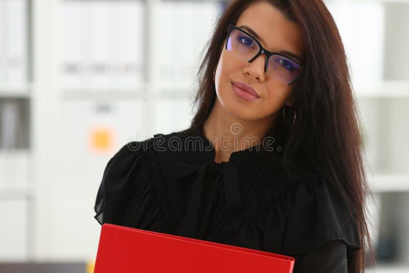 Bella tenuta castana sorridente della donna nel raccoglitore di rosso di armi immagini stock libere da diritti