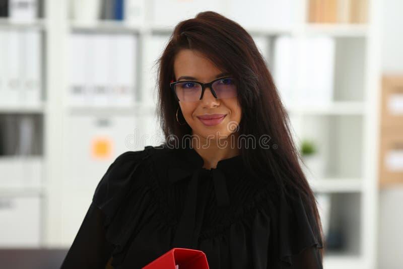 Bella tenuta castana sorridente della donna nel raccoglitore di rosso di armi fotografia stock