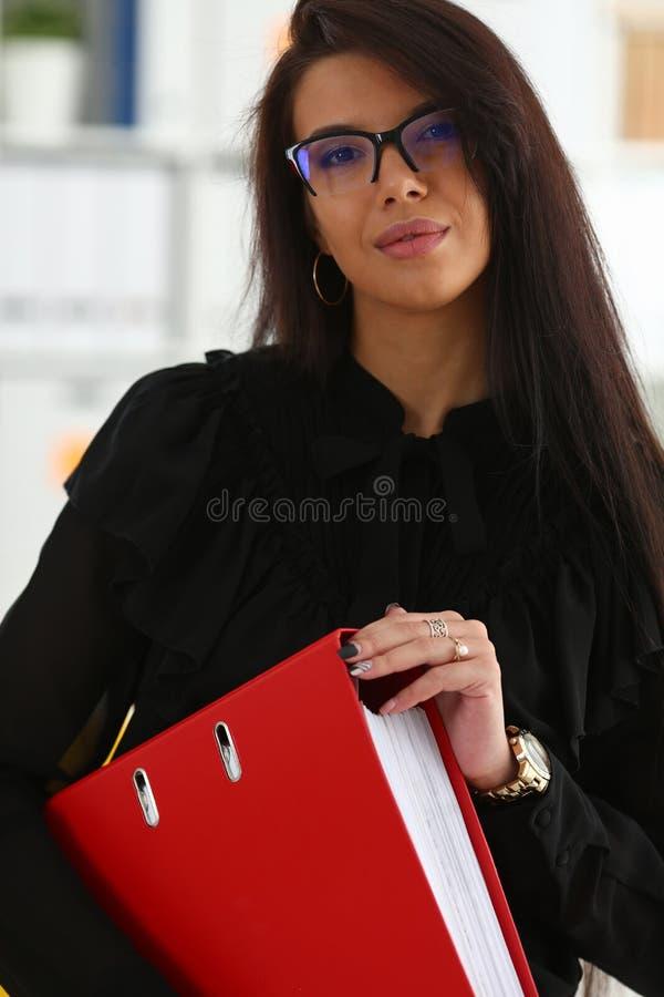 Bella tenuta castana sorridente della donna nel raccoglitore di rosso di armi fotografie stock libere da diritti