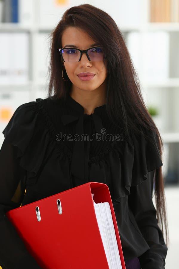 Bella tenuta castana sorridente della donna nel raccoglitore di rosso di armi fotografia stock libera da diritti