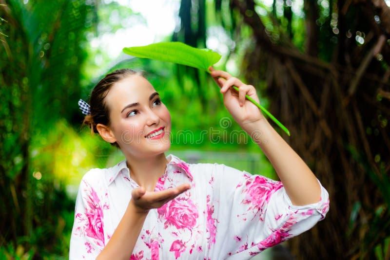 Bella tenuta splendida della donna una foglia per la chiusura della sua testa quando pioggia dei it's fotografie stock