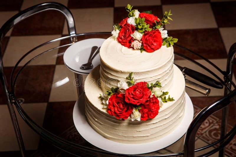 bella torta nunziale sul vassoio di vetro con i piatti ed i cucchiai fotografie stock
