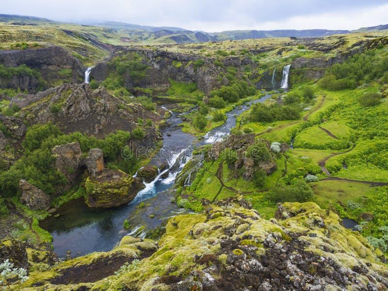 Bella valle Gjain con le rocce variopinte della lava, muschio e vegetazione verde fertile ed acqua blu con le cascate e fotografia stock libera da diritti