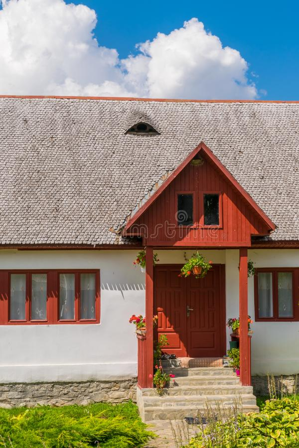 Bella vecchia casa tradizionale rumena con il tetto di mattonelle di legno, il portico dell'entrata anteriore, i fiori e le fines fotografia stock