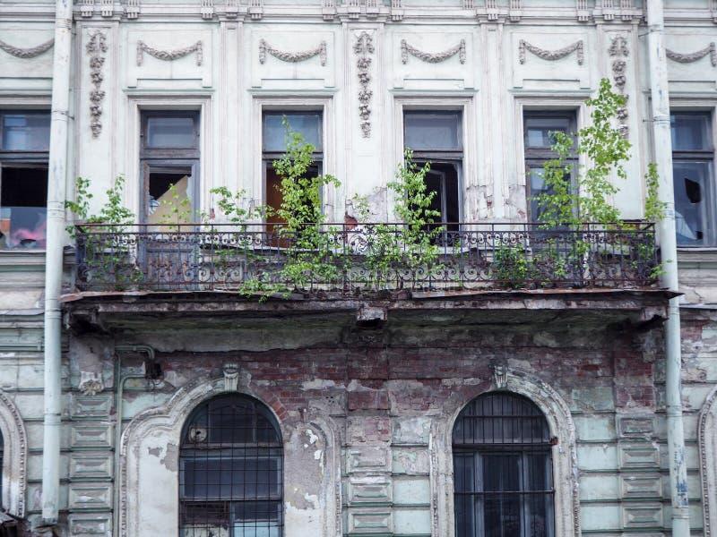 Bella vecchia costruzione abbandonata con le finestre rotte e un balcone rovinato immagine stock libera da diritti