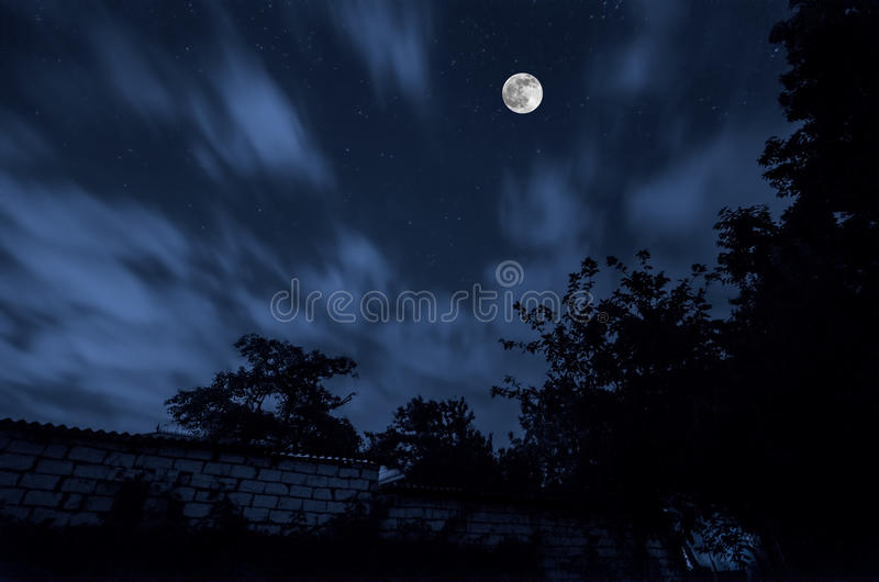 Bella via del villaggio del paesaggio con le costruzioni e gli alberi e grande luna piena al cielo notturno Grande Caucaso Natura fotografia stock libera da diritti