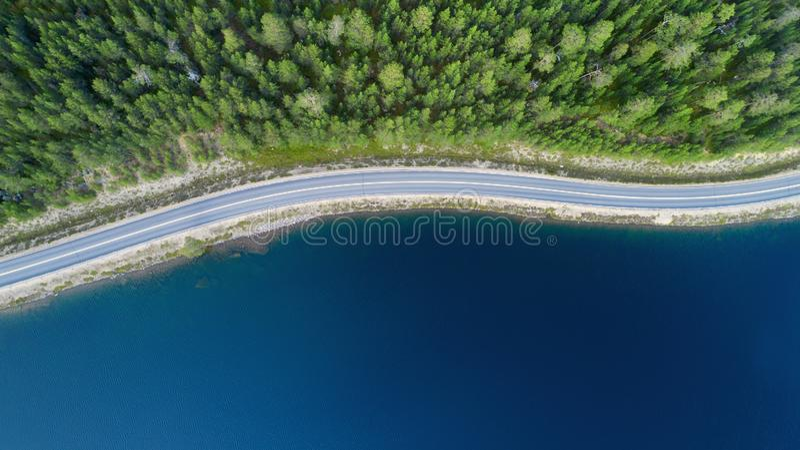 Bella vista aerea della strada fra la foresta verde di estate ed il lago blu in Lapponia fotografia stock