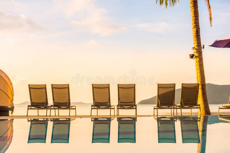 Bella vista all'aperto con l'ombrello e la sedia intorno alla piscina in albergo di lusso e nella località di soggiorno immagine stock libera da diritti