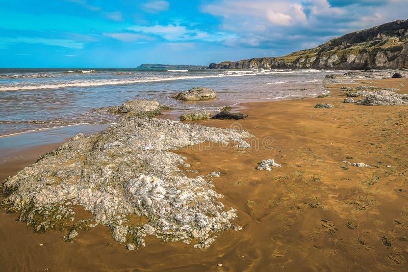 Bella vista Antrim Coast Rocky Downhill Strhill Beach persone che camminano fotografia stock libera da diritti