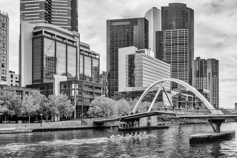 Bella vista in bianco e nero del fiume di Yarra mentre un gruppo degli atleti che remano nel centro di Melbourne, Australia fotografia stock
