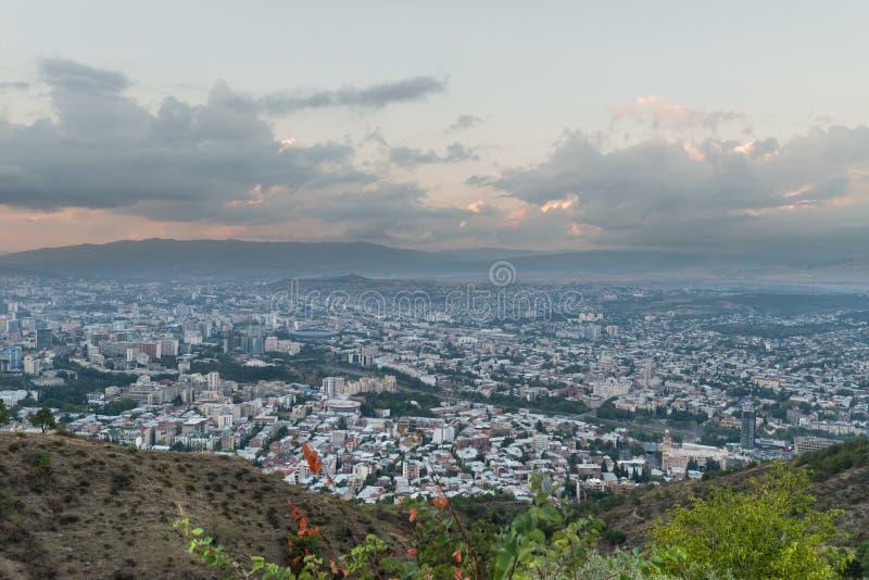 Bella vista dalla collina sulla grande città con le montagne lontano fotografia stock