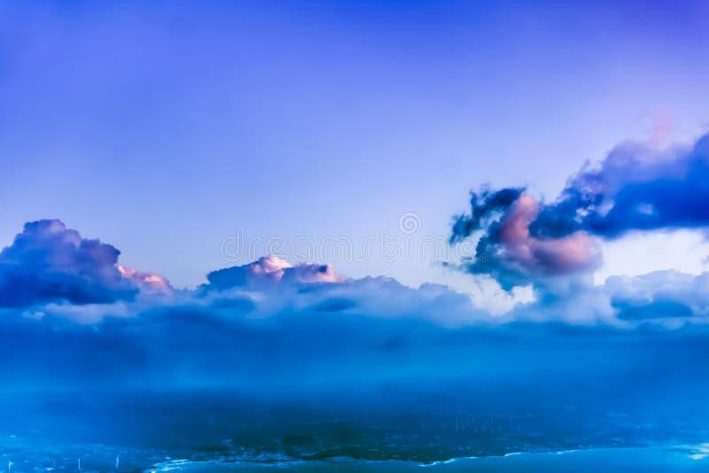 Bella vista dalla finestra dell'aeroplano - nuvola blu rosata in una forma del drago antico fotografie stock