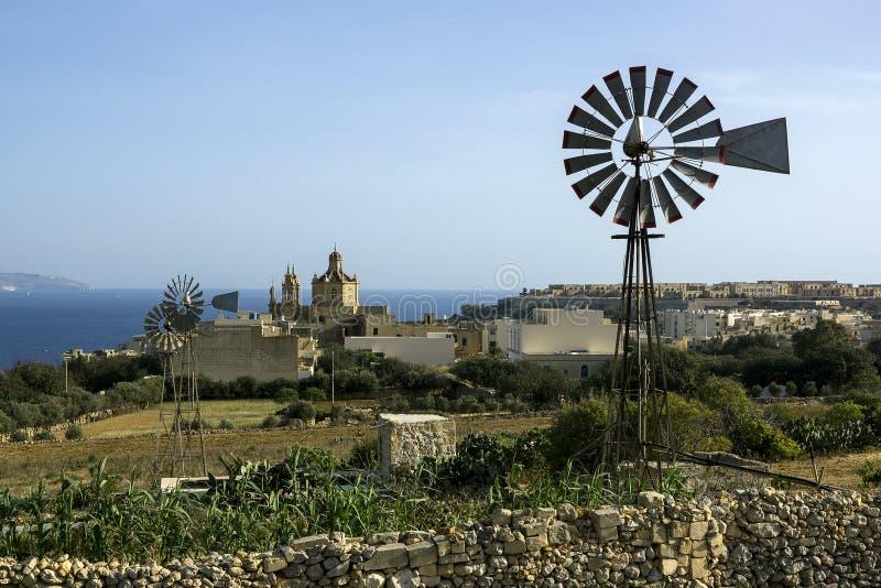 Bella vista del giorno soleggiato maltese della costa in chiaro, del mare, di belle case e dei mulini a vento Su un fondo il mare fotografia stock libera da diritti