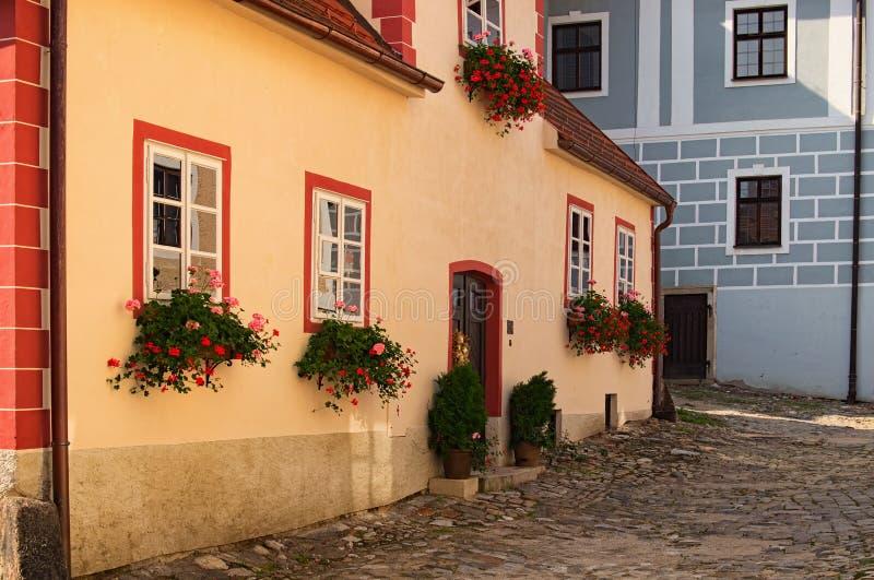 Bella vista del vicolo stretto scenico con le case tradizionali storiche e della via cobbled in Cesky Krumlov di estate immagine stock