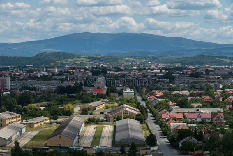 Bella vista della città al piede delle montagne nebbiose verdi contro un cielo nuvoloso blu immagine stock libera da diritti