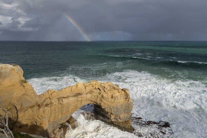 Bella vista della roccia dell'arco lungo la grande strada dell'oceano, Australia, con un arcobaleno nei precedenti immagine stock