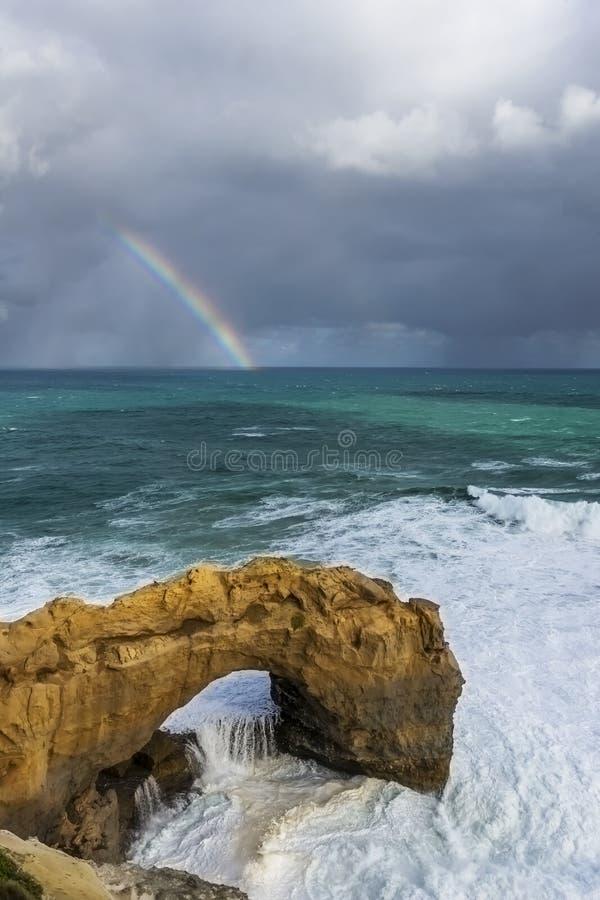 Bella vista della roccia dell'arco lungo la grande strada dell'oceano, Australia, con un arcobaleno nei precedenti immagine stock libera da diritti
