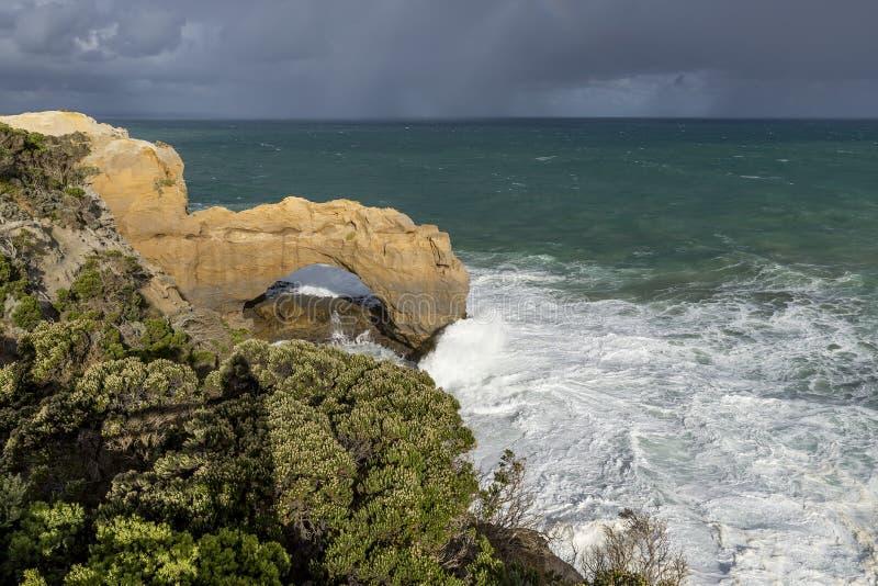 Bella vista della roccia dell'arco lungo la grande strada dell'oceano, Australia, con un arcobaleno nei precedenti fotografia stock libera da diritti