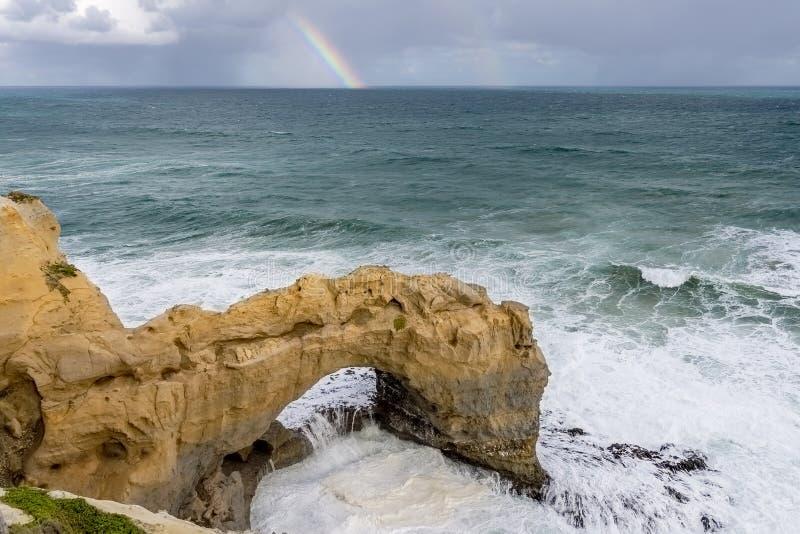 Bella vista della roccia dell'arco lungo la grande strada dell'oceano, Australia, con un arcobaleno nei precedenti fotografia stock