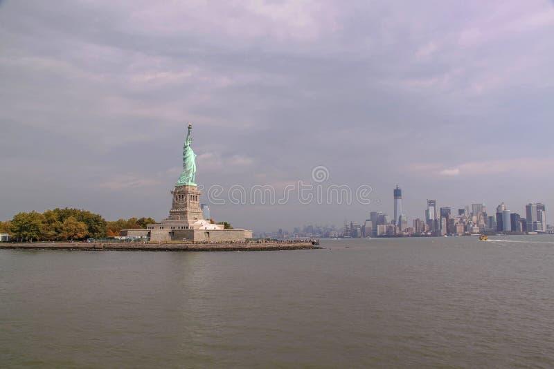 Bella vista della statua della libertà e di Manhattan famose su fondo fotografia stock libera da diritti