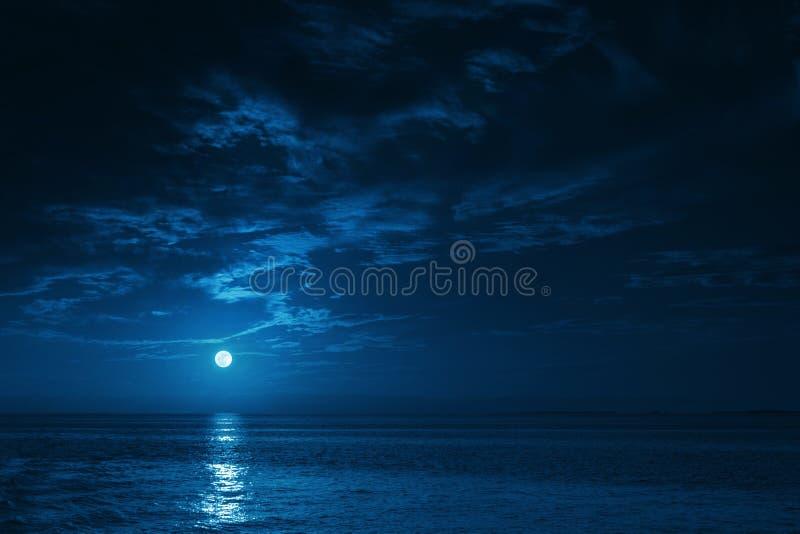 Bella vista di oceano di mezzanotte con le onde di calma e di sorgere della luna fotografia stock libera da diritti