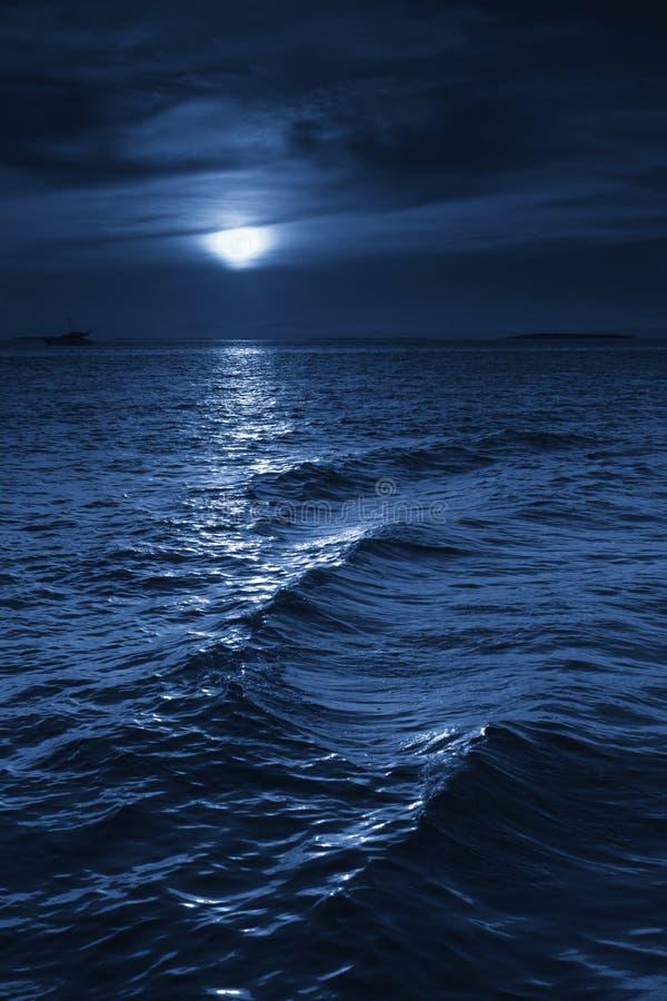 Bella vista di oceano di mezzanotte con le onde di calma e di sorgere della luna fotografie stock libere da diritti