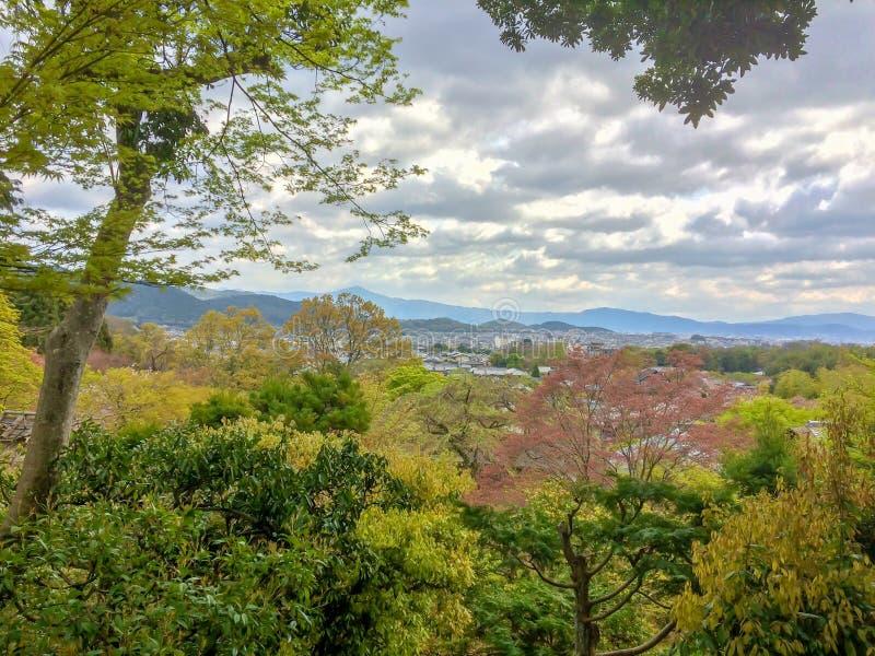 Bella vista di panorama degli alberi variopinti e della cittadina a Kyoto dalla montagna con il cielo nuvoloso fotografia stock