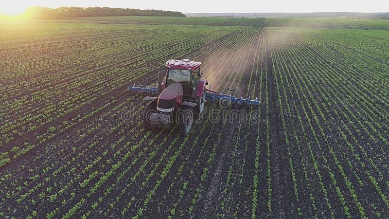 Bella vista di un trattore agricolo sul campo al tramonto immagini stock