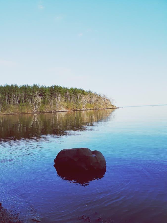 Bella vista sul mare al tramonto di un giorno di estate con una pietra nella priorità alta fotografie stock