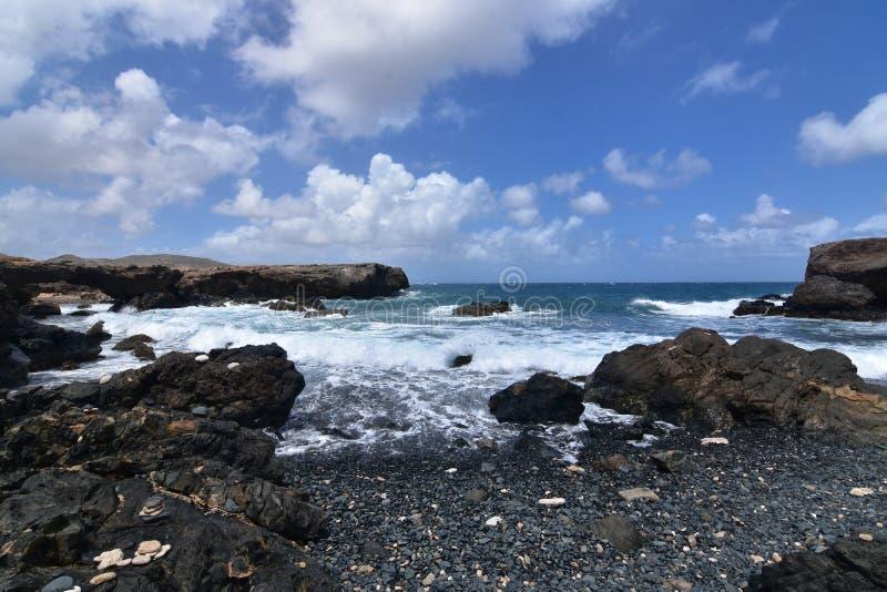 Bella vista sul mare del nero Pebble Beach del ` s di Aruba in Aruba immagine stock