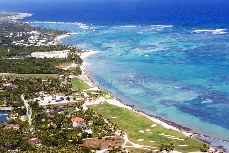 Bella vista superiore: mar dei Caraibi del turchese, spiaggia sabbiosa, palmeto, hotel un giorno soleggiato luminoso immagini stock libere da diritti