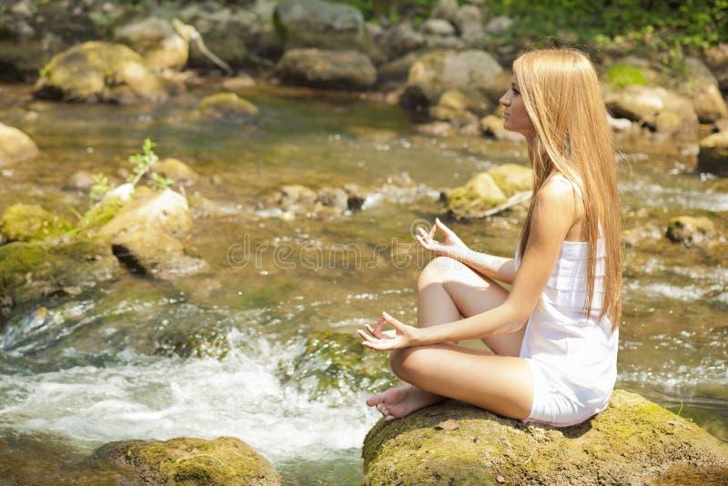 Bella yoga di Practive della donna sul fiume in natura fotografia stock libera da diritti