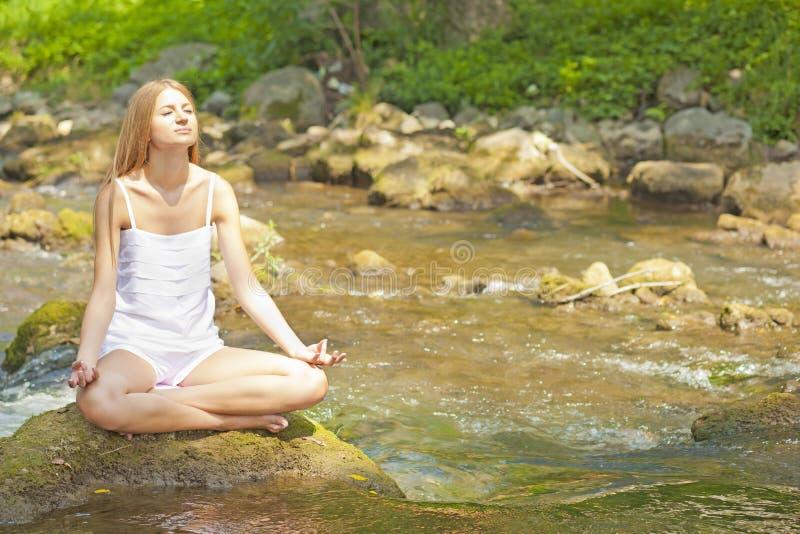 Bella yoga di Practive della donna sul fiume in natura fotografie stock