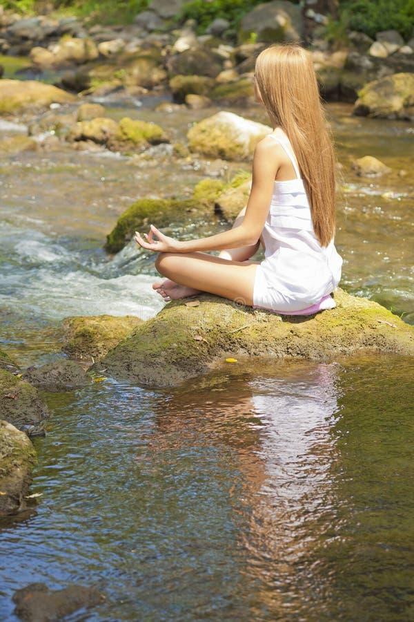 Bella yoga di Practive della donna sul fiume in natura immagini stock
