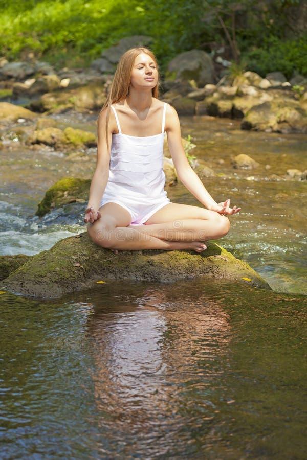 Bella yoga di Practive della donna sul fiume in natura fotografia stock