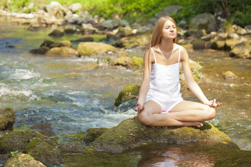Bella yoga di Practive della donna sul fiume in natura immagine stock