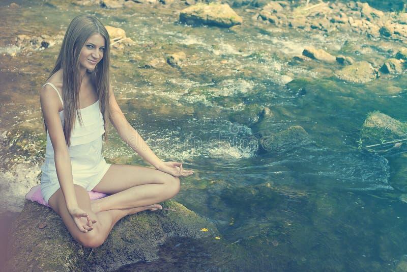 Bella yoga di Practive della donna sul fiume in natura immagine stock libera da diritti