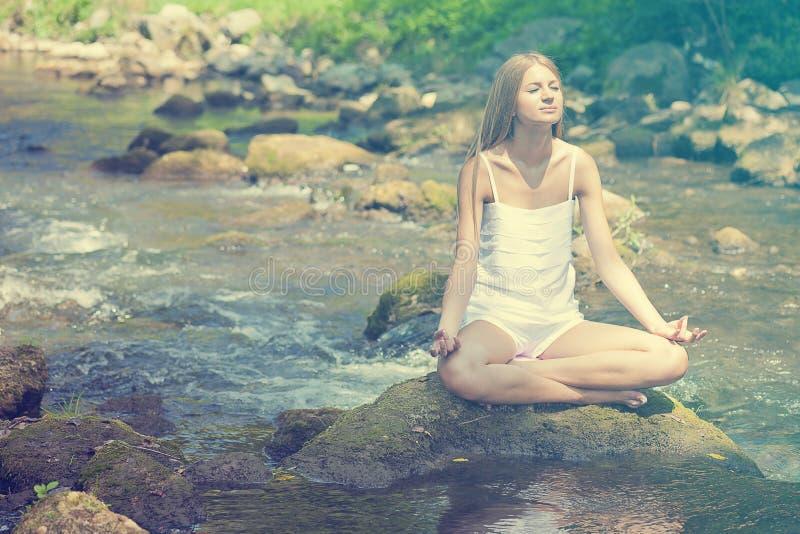 Bella yoga di Practive della donna sul fiume in natura fotografie stock libere da diritti