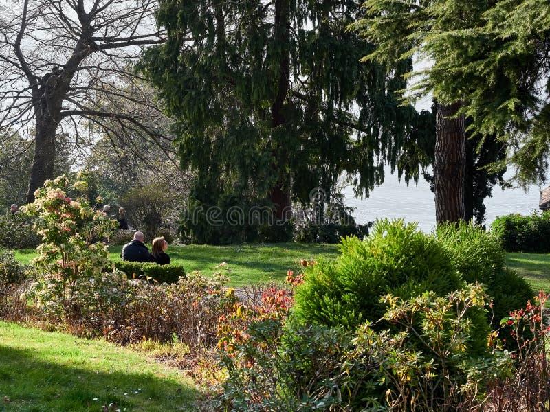 Bellagio, Itali? 30 Maart het Paarzitting van 2019 in een tuin aan comtemplate de mening van Meer Como stock afbeelding