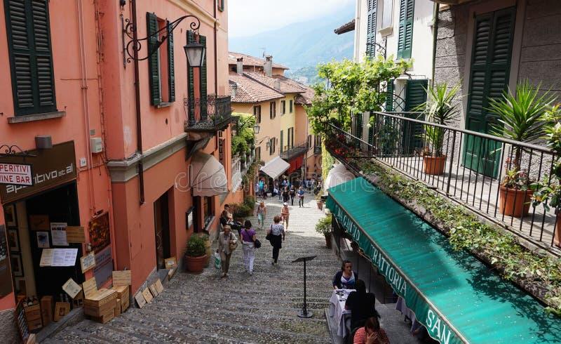 BELLAGIO, ITALIA - 14 DE MAYO DE 2017: turistas en la opinión pintoresca de la calle de la pequeña ciudad de Salita Serbelloni en foto de archivo libre de regalías