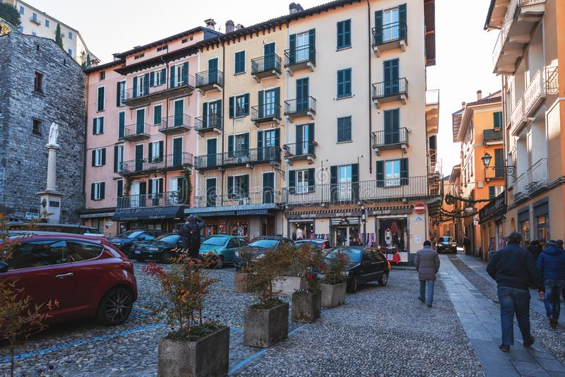 People are visiting raditional Italian narrow streets with beautiful architecture of cities around Como lake royalty free stock image