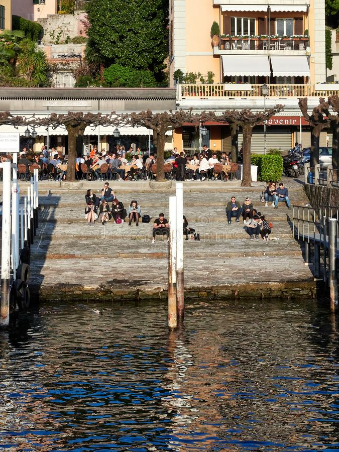 Bellagio, Italy  March 30 2019 Tourists and Local sits at the stoned man made shore to observe the sunset in Bellagio Lake Como. Bellagio, Italy  March 30 2019 royalty free stock image