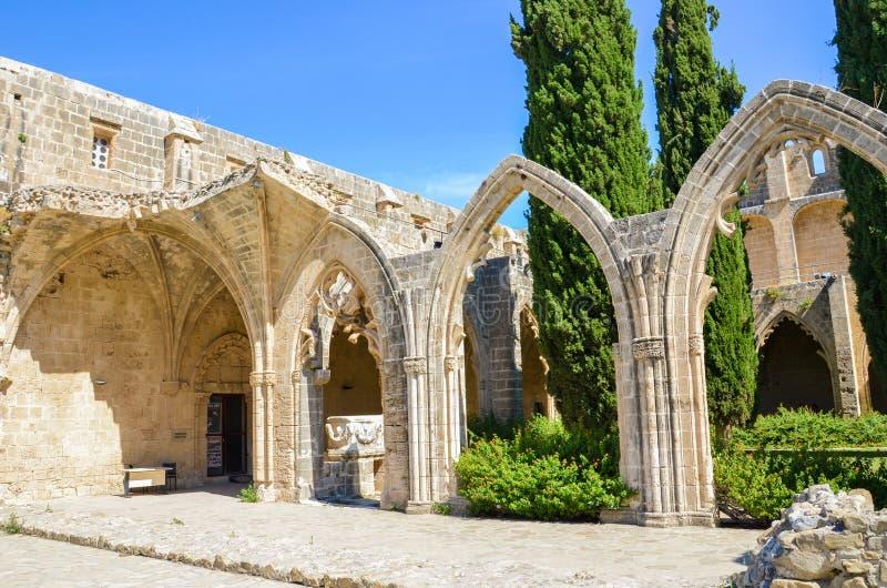 Bellapais, Chipre - 4 de outubro de 2018: Ruínas da abadia histórica de Bellapais com paredes e os arcos antigos O monastério med fotografia de stock royalty free