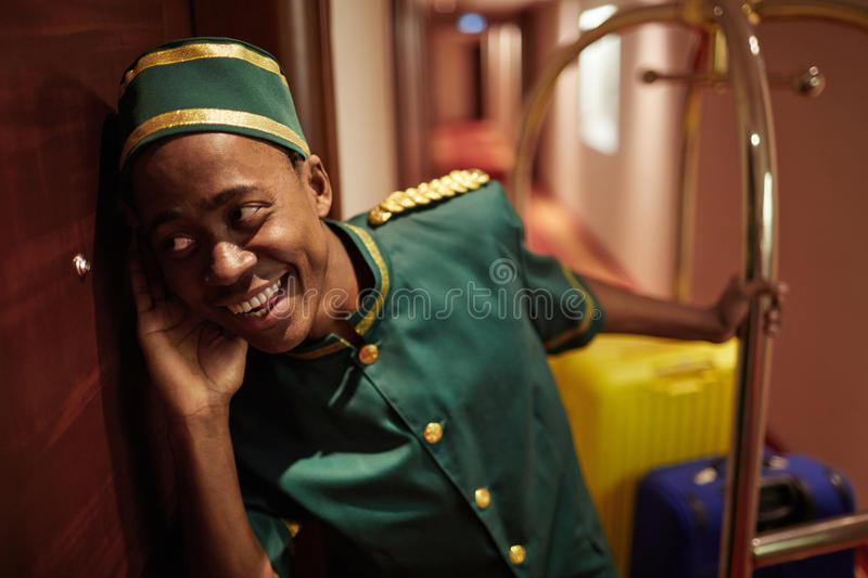 Bellboy Delivering Bags to Hotel Rooms. Portrait of young African boy working as bellhop in luxury hotel, listening at the room door delivering luggage stock photos