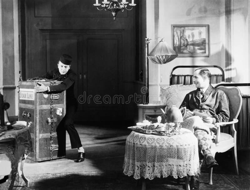 Bellboy ono zmaga się z bagażnikiem w gościa pokoju (Wszystkie persons przedstawiający no są długiego utrzymania i żadny nierucho zdjęcie stock