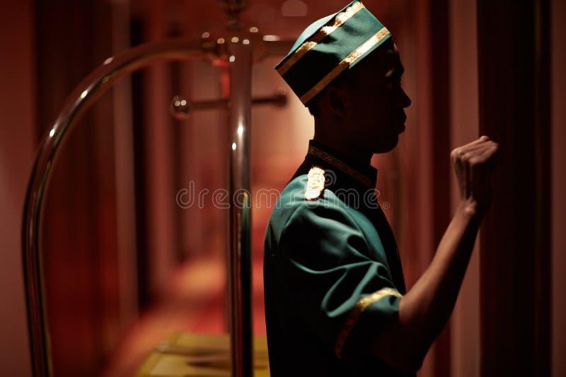 Bellboy pukanie na Izbowym drzwi w hotelu obraz stock