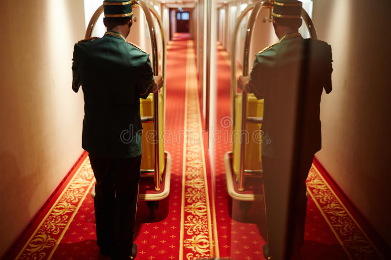 Bellboy Pushing Luggage Cart in Hotel Hallway. Back view portrait with mirror reflection of bellboy pushing luggage cart in hotel hallway, delivering bags to royalty free stock photos
