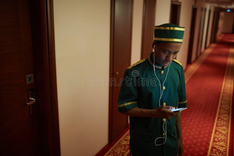 Bellboy Słucha muzyka w Hotelowym Hall obraz stock